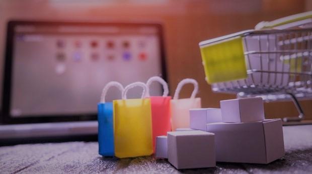 Foto mit Einkaufstaschen, Einkaufwagen und Rechner. Verdeutlicht die Vielfalt der Einkaufsmöglichkeiten und Customer Experience